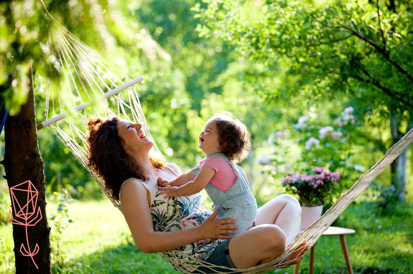 Mom and baby sitting in a hammock and laughing with green garden in background